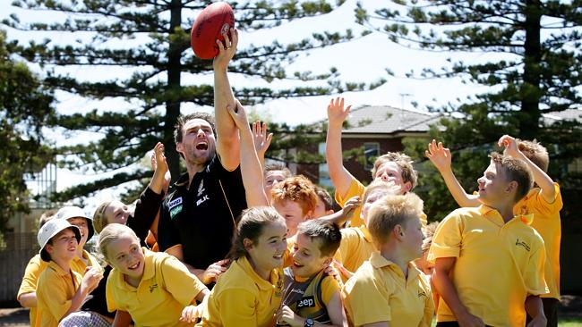 Former captain Chris Newman has a bit of fun with students from Warrnambool Primary school.