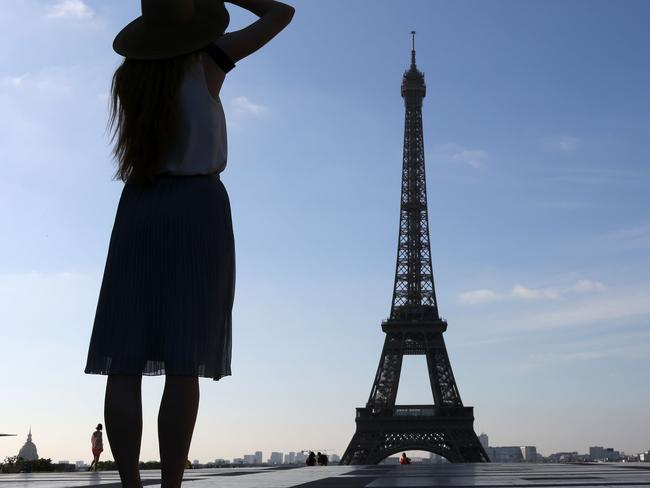 A woman takes pictures of the Eiffel tower from the Human Right square (aka the Trocadero Plaza) as the sun rises on June 26, 2017, in Paris. / AFP PHOTO / LUDOVIC MARIN