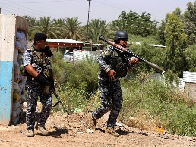 Defensive ... Iraqi federal policemen patrol the town of Taji, about 20 kilometres north of Baghdad, June 26, 2014. Picture: Karim Kadim