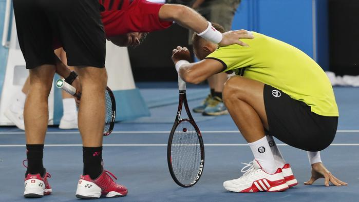 Switzerland's Stan Wawrinka, left, checks on Slovakia's Martin Klizan after he was struck by the ball during their first round match at the Australian Open tennis championships in Melbourne, Australia, Monday, Jan. 16, 2017. (AP Photo/Kin Cheung )