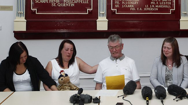 Family members of murdered British soldier Lee Rigby, from left to right, sister Sara McClure, his mother Lyn, stepfather Ian, and his wife Rebecca Rigby, in front of a roll of honour board showing the deeds and sacrifices of the regiment, as his stepfather reads a statement during a press conference at the Regimental HQ of his unit. (AP Photo/Dave Thompson)