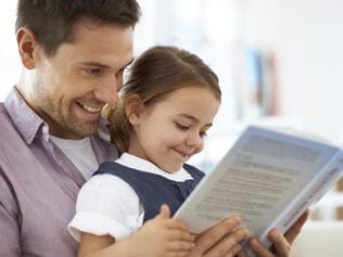 Shot of a young father reading a book with his daughter