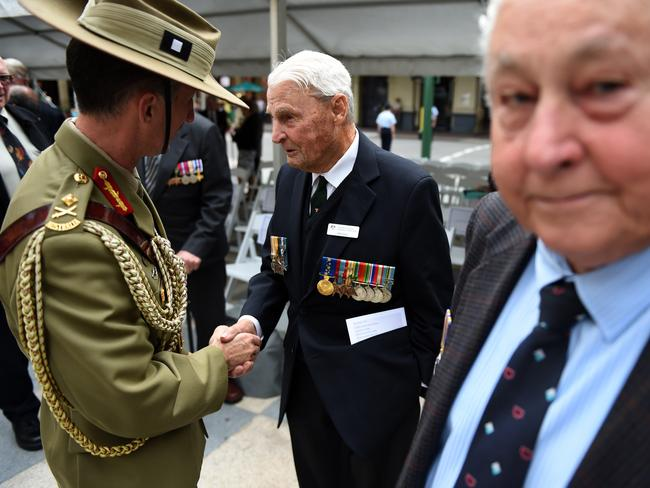 Major General Stewart Smith (left) shakes hands with WWII veteran Bill Corey during a Victory in the Pacific Day 70-year anniversary commemoration ceremony in Brisbane. Picture: AAP