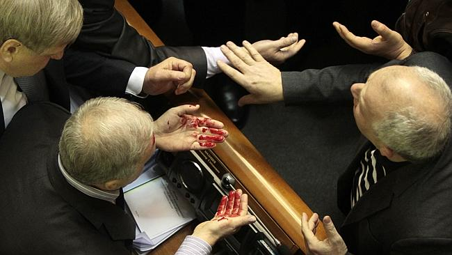 Ukrainian pro-government lawmaker Vladimir Malyshev wipes the blood from his face after a scuffle in Ukraine's parliament in Kiev. Picture: Sergei Chuzavkov
