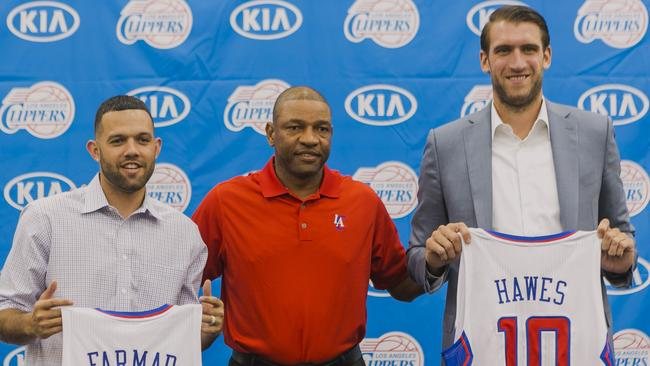 Los Angeles Clippers head coach Doc Rivers, centre, poses with his new players, free agent guard Jordan Farmar, left and centre Spencer Hawes, right.
