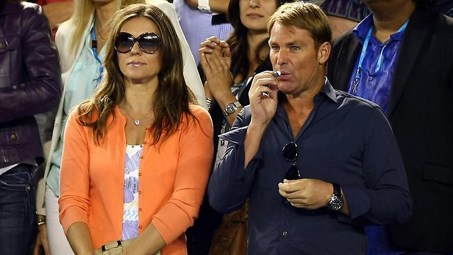 Front row seats: Liz Hurley is straight-faced while Warnie keeps those kissing lips moist at the Aussie Open. Picture: Splash News