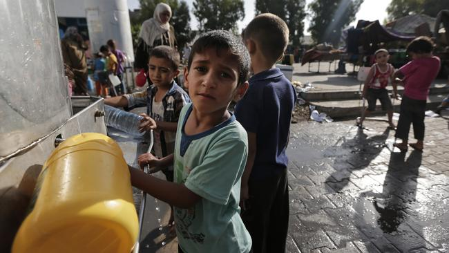 Displaced Palestinian children collect water, at the Abu Hussein UN school, in Jebaliya refugee camp, northern Gaza strip, hit by an Israeli strike earlier on July 30.