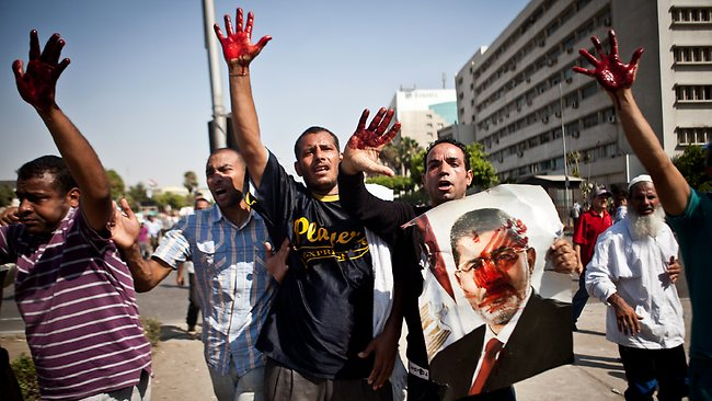Islamist protesters, one holding a picture of ousted president Mohammed Morsi, hold up blood-stained hands after troops opened fire on a protest in front of the Republican Guard headquarters in Nasr City, Cairo, Egypt.