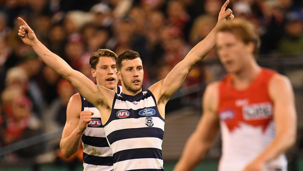 Sam Menegola celebrates a Geelong goal with Mark Blicavs.