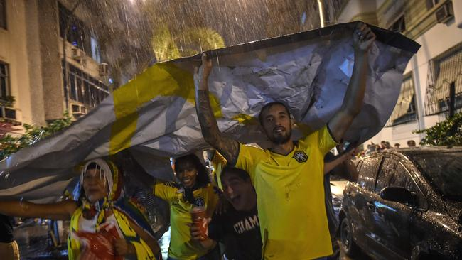 Brazilian fans take cover from the rain after watching the game.