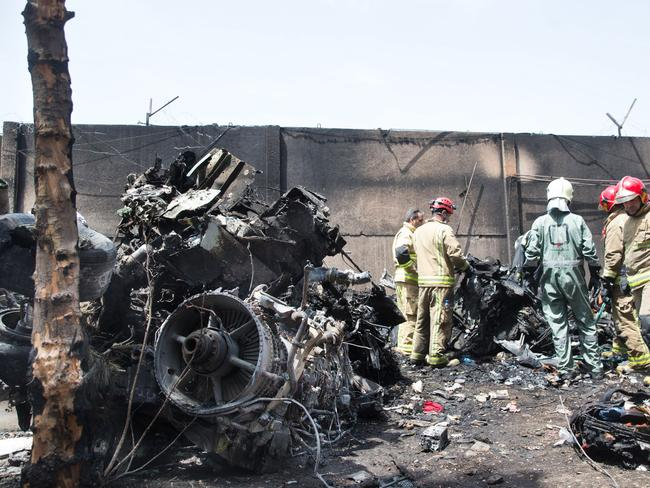 Crash ... a picture obtained from Iran's ISNA news agency shows Iranian rescue personnel inspecting the scene of a plane crash near Tehran's Mehrabad airport. Picture: AFP/ISNA