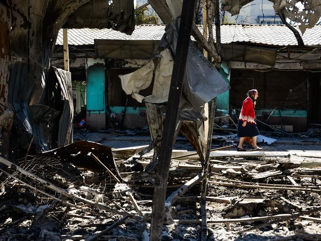 Ruins ... a woman passes by shops burned by shelling near the train station in Donetsk, Ukraine.