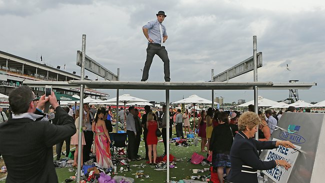 A racegoers dances on the roof of a shelter after the Melbourne Cup.