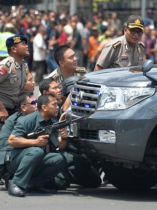 Targeted ... Indonesian police take position behind a vehicle as they pursue suspects aft
