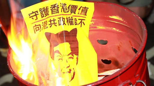 "A poster with a picture of Hong Kong chief executive Leung Chun-ying reading ""Guard the values of Hong Kong, tell Hong Kong people to say no to communist authority"" is burnt by protesters."