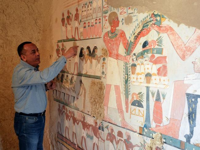 Mustafa al-Waziri, Director General of Luxor's Antiquities, with an ancient Egyptian mural found at the newly discovered tomb. Photo: AFP/STRINGER