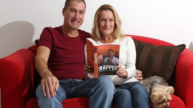 Marcus and Julie Lee at their Burleigh Waters home with dog Dudley and their new book Trapped. Pic: Glenn Hampson