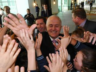 Australian Prime Minister Malcolm Turnbull high fives kids from Drummoyne Public School at Parliament House in Canberra, Thursday, June 22, 2017. (AAP Image/Lukas Coch/POOL) NO ARCHIVING