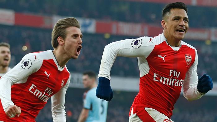 Arsenal's Chilean striker Alexis Sanchez (R) celebrates with Arsenal's Spanish defender Nacho Monreal (2nd L) after scoring their late winner from the penalty spot during the English Premier League football match between Arsenal and Burnley at the Emirates Stadium in London on January 22, 2017. Arsenal won the game 2-1. / AFP PHOTO / Ian KINGTON / RESTRICTED TO EDITORIAL USE. No use with unauthorized audio, video, data, fixture lists, club/league logos or 'live' services. Online in-match use limited to 75 images, no video emulation. No use in betting, games or single club/league/player publications. /