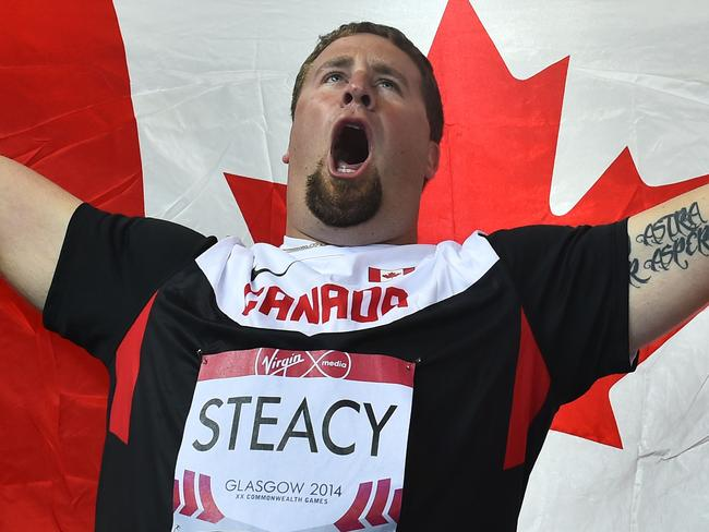 Canada's Jim Steacy celebrates winning the men's hammer throw.