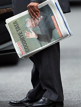 A security officer holds a copy of a newspaper with a picture of former president Nelson Mandela, outside his home in Johannesburg. Picture: AP Photo/Themba Hadebe