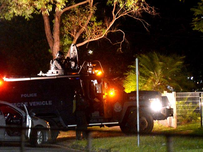 Heavily armed police approach a home last night hunting for the killer of a man in Heckenberg in Sydney's southwest. Photo Jeremy Piper