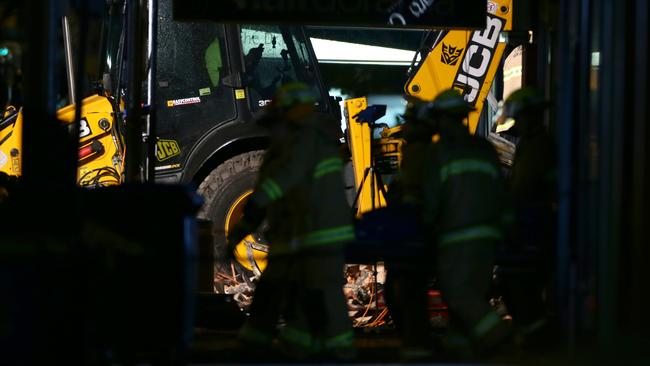 Firefighters remove the body of a man from the explosion zone in Rozelle last night. Picture: Bill Hearne