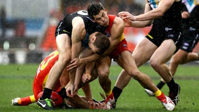Jaeger O'Meara copped a hard hit as the bodies clashed hard in the slippery conditions. Picture: David Clark