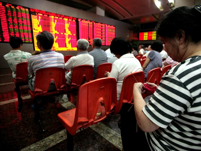 An investor knits while watching stock quotes at a securities trading firm in Shanghai on Thursday.