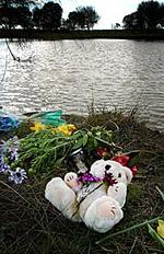 <p>A toy bear lies among flowers at the side of the farm dam where the brothers died on September 4, 2005. Picture: Jon Hargest</p>