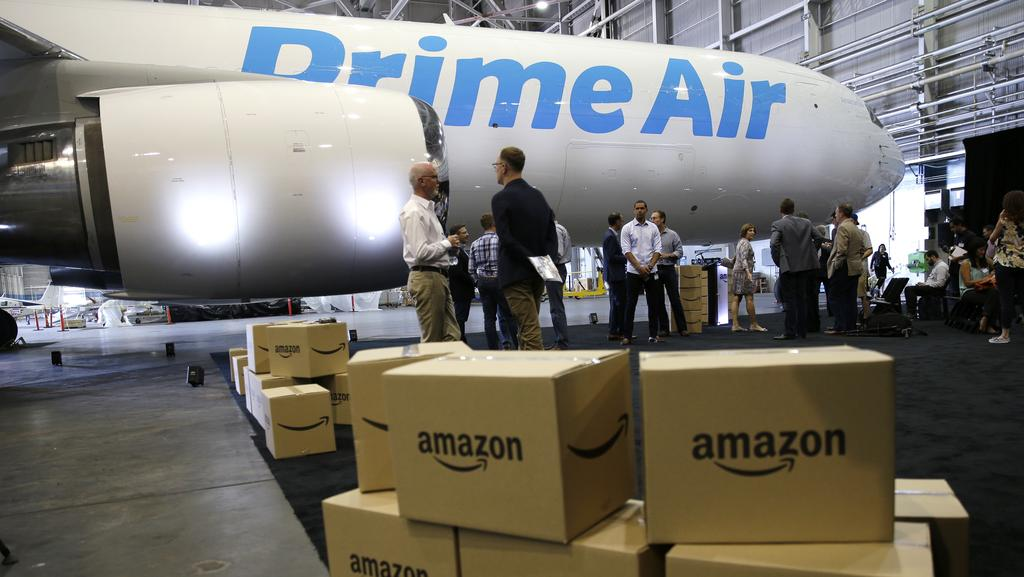 "Amazon boxes stacked near a Boeing 767 Amazon ""Prime Air"" cargo plane on display in a Boeing hangar in Seattle. Picture: Ted S. Warren/AP"