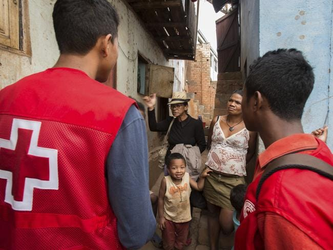 Red Cross volunteers talk to villagers about the plague outbreak. Picture: AP/Alexander Joe