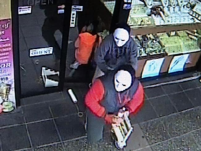 The two men flee the scene of the second robbery carrying a display stand from the store.