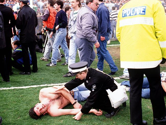 Horror ... fans lie injured on the pitch after being hauled from the crowded pens at Hillsborough. Jurors have been told the new inquests could take up to a year.