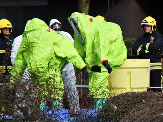 Members of the fire brigade are helped out of their green biohazard suits by colleagues in white protective coveralls after an operation to reattach the tent over the bench in Salisbury. Picture: Ben Stansall/AFP