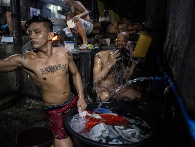 An inmate cooks his dinner as other detainees take a bath inside the Quezon City jail. Picture: Ayee Macaraig