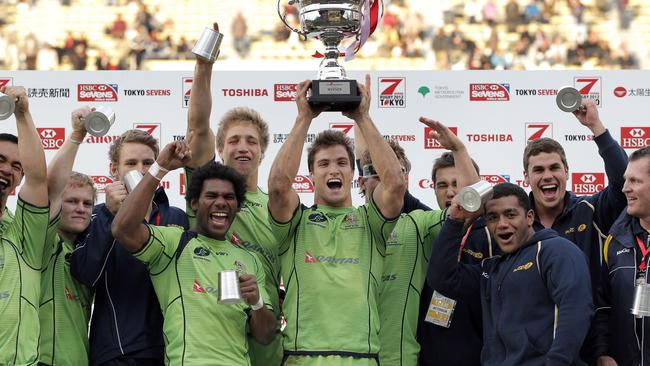 Ed Jenkins, c, raises the winner's trophy as Australia celebrate after defeating Samoa in the final of the Tokyo Sevens, 2012.