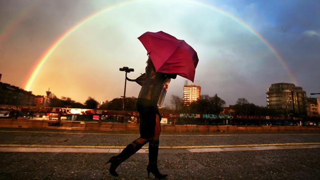 A rainbow is seen in the background while a woman holds an umbrella as she walks in downtown Sofia.