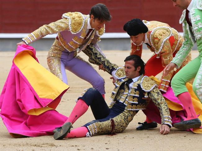 Feeling the pain ... Assistants help Spanish matador David Mora after he was injured during a bullfight of the San Isidro Feria at the Las Ventas bullring in Madrid.