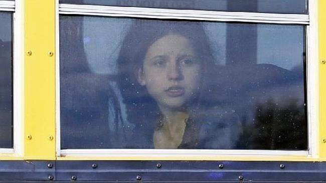 A student stares out a bus window as it arrives at a church to be reunited with family after students from nearby Arapahoe High School were evacuated. Picture: AP