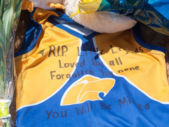 A football jumper left among the cards and flowers as a tribute at the wharf memorial. Photo: Ivon Perrin