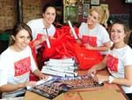 Sharks supporters Packing the The Advertiser showbags. Picture: Mark Brake