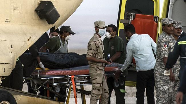 Grisly work ... Egyptian paramedics load the corpses of victims of a Russian passenger plane crash in the Sinai Peninsula, into a military plane at Kabret military air base by the Suez Canal. Picture: Khaled Desouki/AFP