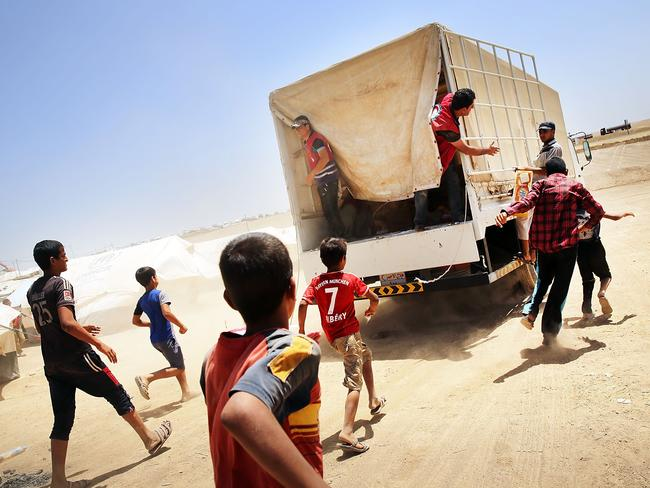 Desperate Iraqi's at the Khazair displacement camp for those caught-up in the fighting in and around the city of Mosul, chase a Red Crescent society truck delivering food. Photo: Spencer Platt/Getty Images