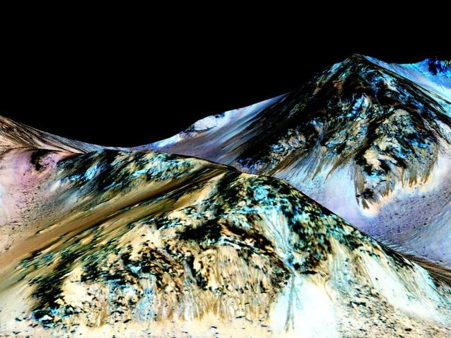 Mountain flow ... A NASA image shows dark, narrow, 100-metre-long streaks called recurring slope lineae flowing downhill on Mars, believed to have been formed by flowing water. Picture: AFP