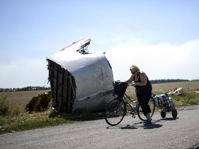 Wreckage left over ... a woman walks with her bicycle near the crash site of the Malaysia Airlines Flight MH17 in the village of Hrabove (Grabovo). Picture: AFP