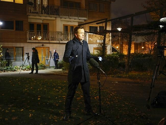A TV journalist conducts a live broadcast outside a South London block of flats.