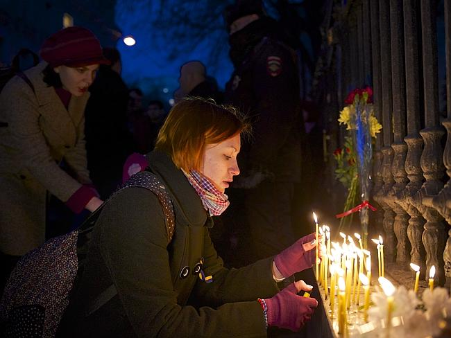 A woman lights candles in memory of the victims of clashes between police and protesters.