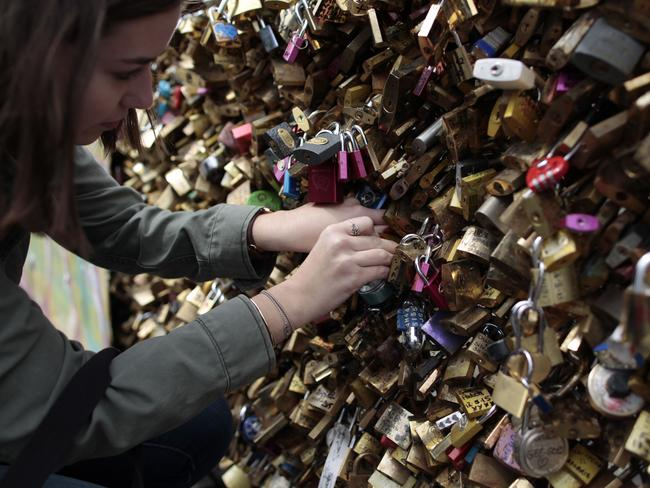 Lovestruck ... a woman a locks a padlock on the 'Pont Notre Dame' on May 29, 2015. Picture: AFP/Charly Triballeau