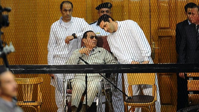 Egypt's former dictator Hosni Mubarak and his two sons Alaa (R) and Gamal stand behind bars during their trial at the Police Academy in Cairo. Picture: AFP